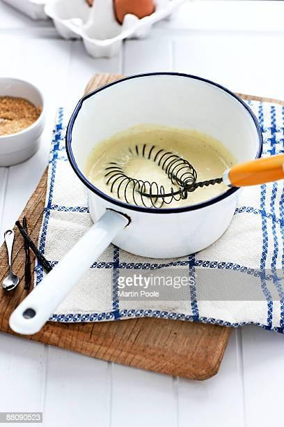 Custard in pan on chopping board