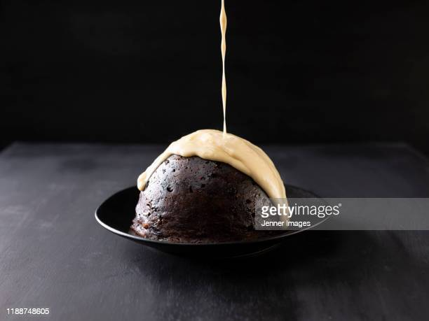 custard pouring over christmas pudding. - gourmet stock pictures, royalty-free photos & images