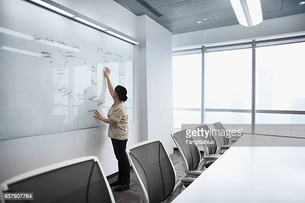custodial staff wiping white board clean in meeting room - commercial cleaning stock photos and pictures