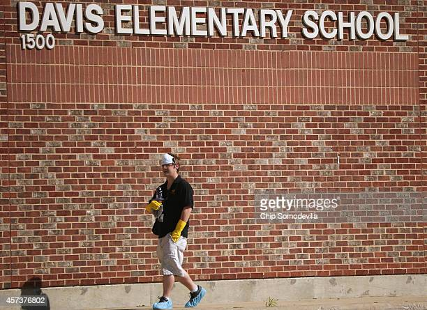 A custodial worker leaves after cleaning Davis Elementary School which remains closed after it was discovered that a health care worker who treated...