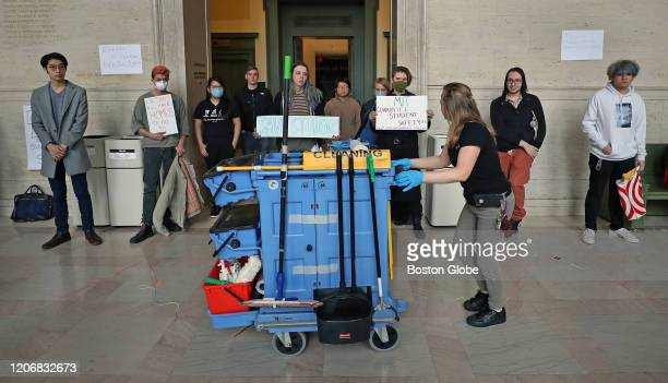 MIT custodian with her cleaning cart walks past MIT students during an MIT international student demonstration on March 12 2020 in Cambridge MA...