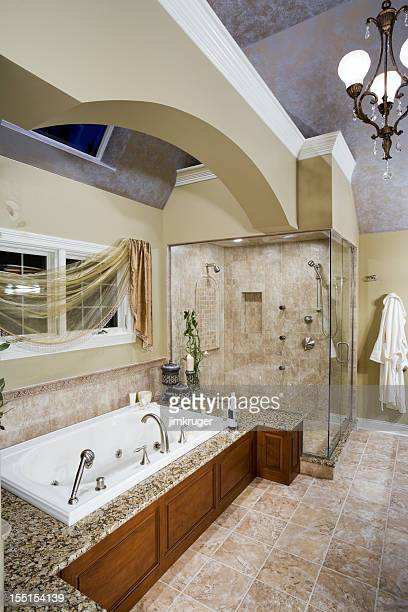Custom neutral toned master bathroom with jacuzzi tub.