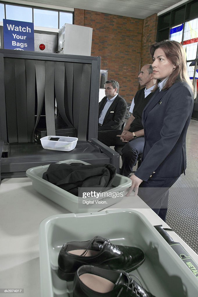Custom Officers by a Metal Detector in an Airport : Stock Photo