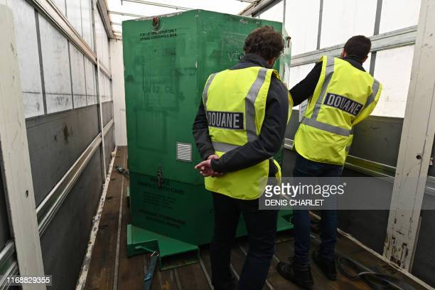 Custom officers check the loading of a truck during a day of test in case of Brexit at the exit of the Channel tunnel in Calais, northern France on...