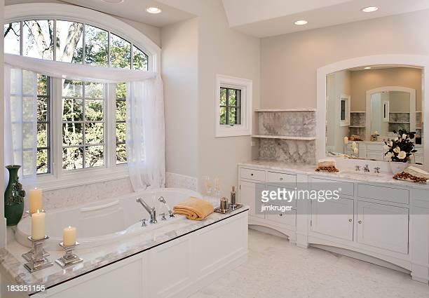 custom white toned master bathroom with hot tub tub. - bathroom stock pictures, royalty-free photos & images