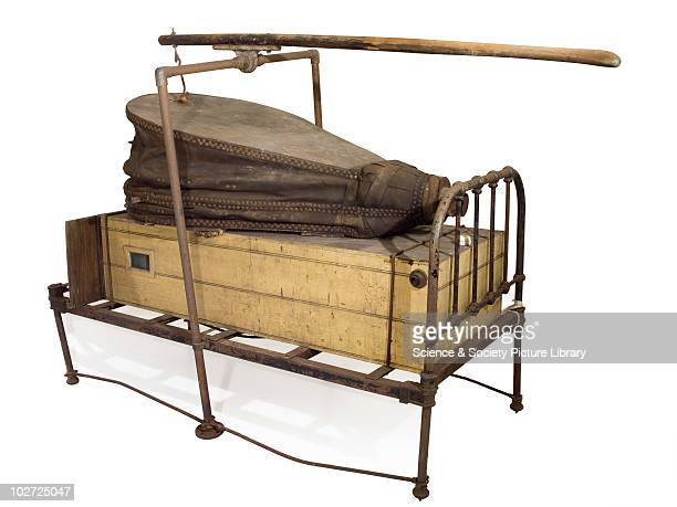 Custombuilt iron lung Custombuilt iron lung consisting of wooden chamber fixed to iron bedstead and ventilated by means of handcranked leather forge...