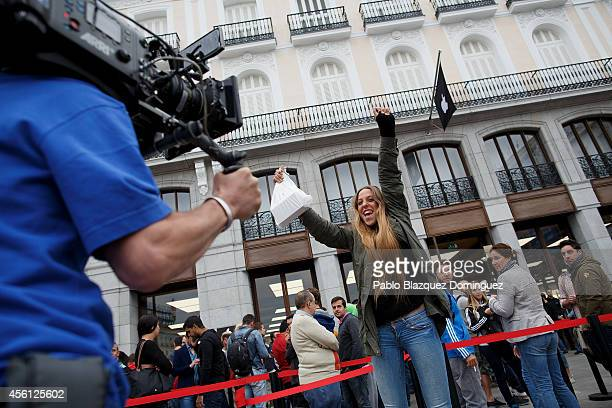 A customer acts for a tv production after buying a new iPhone at Puerta del Sol Apple Store as Apple launches iPhone 6 and iPhone 6 Plus on September...