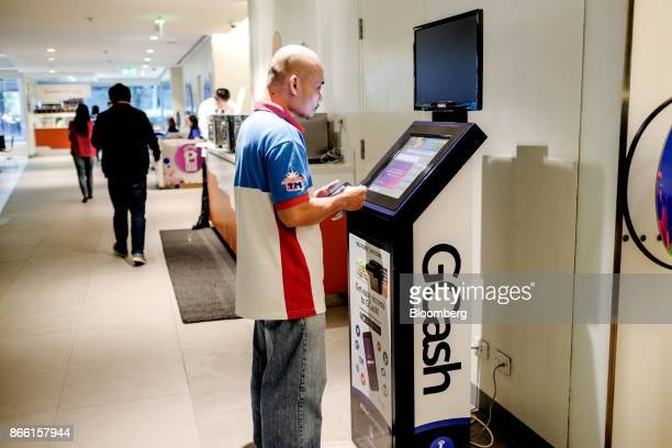 A customer adds credit to his mobile phone by using a Globe Telecom Inc GCash topup machine in Taguig city Metro Manila the Philippines on Monday Oct...