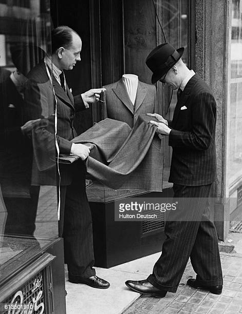 A customer and a salesman stand in the doorway of a clothing store which was damaged during a World War II air raid