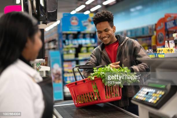 cliente e caixa no check-out no supermercado - consumismo - fotografias e filmes do acervo