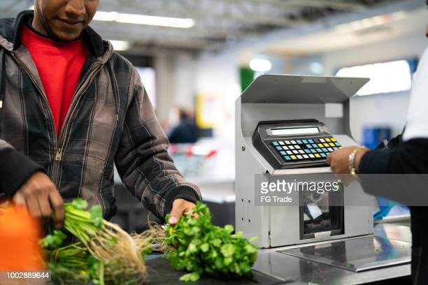 customer and cashier in checkout at supermarket - megastore stock photos and pictures