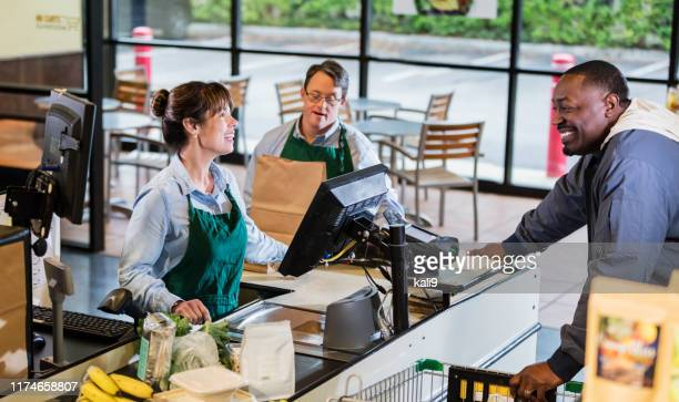 customer and employees at supermarket checkout - persons with disabilities stock pictures, royalty-free photos & images