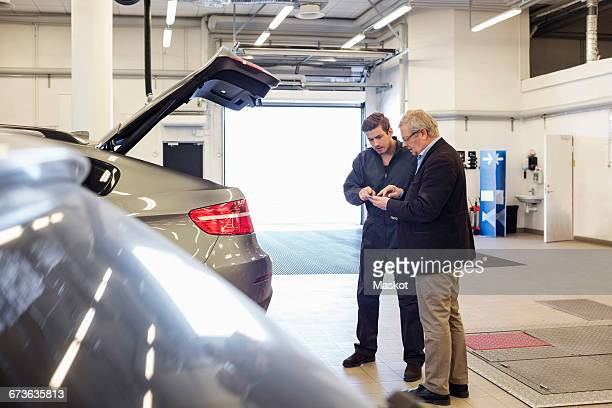 Customer and mechanic using mobile app while standing by car in repair shop