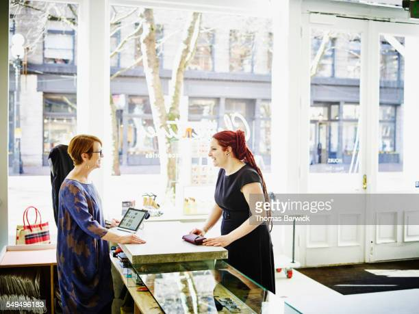 Customer and shop owner in discussion in boutique