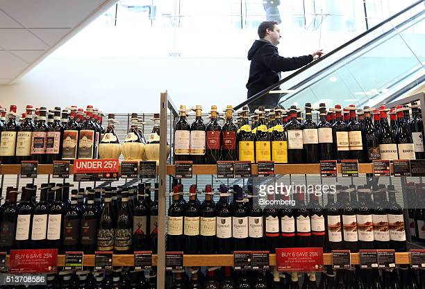 A customer ascends an escalator behind a shelf displaying bottles of wine inside a branch of Marks Spencer Group Plc in London UK on Wednesday March...
