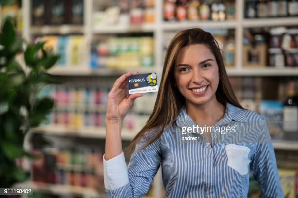 Customer at a food market holding a rewards card
