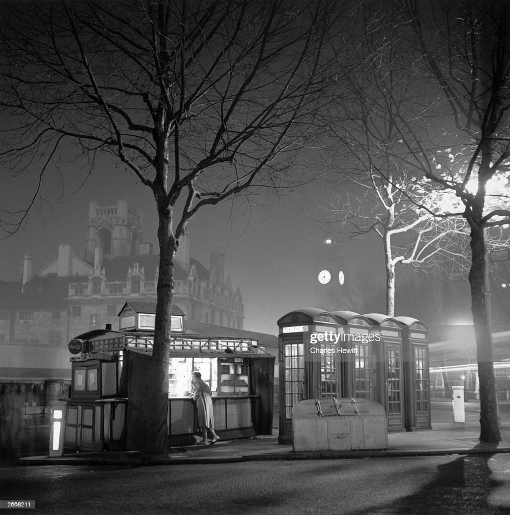 A customer at a late-night coffee stall on the junction of Totrill and Victoria Street, London, with the illuminated face of Big Ben in the background. Original Publication: Picture Post - 6150 - Coffee Stalls - unpub.