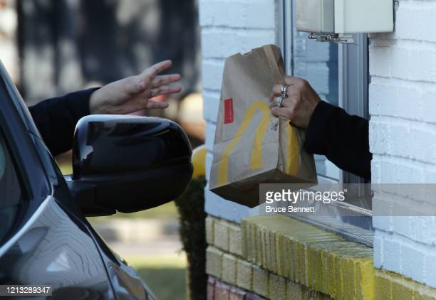 Customer at a McDonald's uses the drive up window on March 18, 2020 in Hicksville, New York. The World Health Organization declared COVID-19 a global...