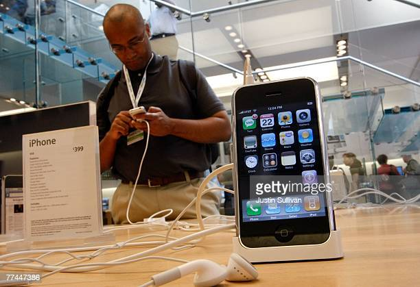 A customer at an Apple Store inspects the Apple iPhone October 22 2007 in San Francisco California Apple stock surged $394 to close at a record high...