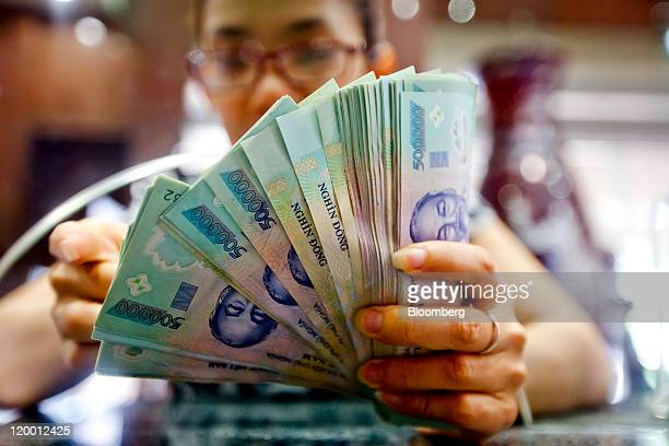 Customer at Joint-Stock Commercial Bank for Foreign Trade of Vietnam, or Vietcombank, makes a deposit of dong bank notes in Hanoi, Vietnam, on...