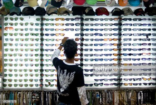 Customer at sunglass stall at Kata Beach evening market.