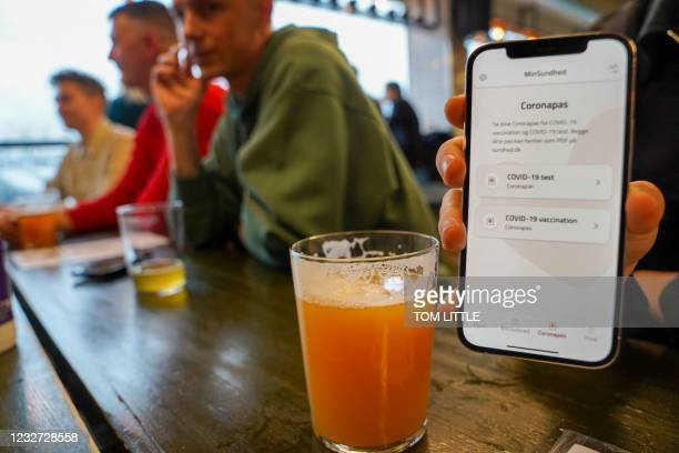 Customer at the Danish craft brewery Mikkeller's pub Warpigs in Copenhagens former Meatpacking District shows their Corona pass, an app on their...