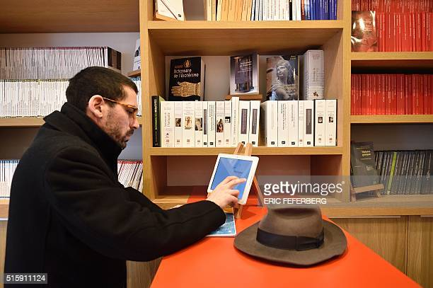 A customer at the new bookstore of the Presses Universitaires de France uses a tablet to choose a book to be printed on the spot in Paris on March 16...