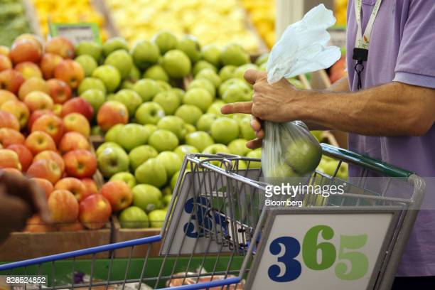 A customer bags apples during the grand opening of a Whole Foods Market 365 location in Santa Monica California US on Wednesday Aug 9 2017 The fifth...