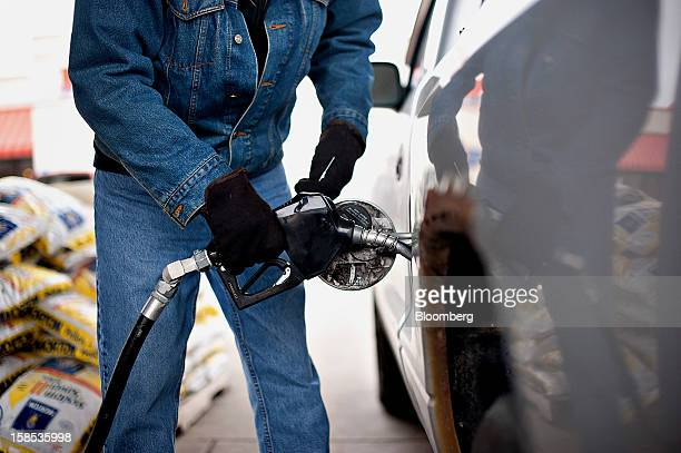 Customer Bob Dalziel removes a gas pump from his truck after filling up at a gas station in Princeton Illinois US on Tuesday Dec 18 2012 Retail...