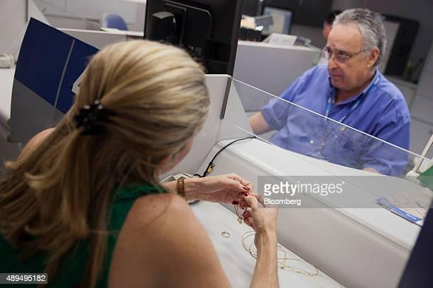 A customer brings gold jewelry to appraiser Carlos Monteiro at a governmentrun pawnshop in the Cinelandia branch of the stateowned Caixa Economica...