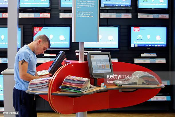 A customer browses a catalogue at an Argos store operated by Home Retail Group Plc in Enfield UK on Wednesday Sept 7 2011 Home Retail Group Plc owner...