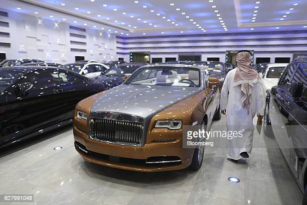 A customer browses a collection of luxury automobiles including a Rolls Royce centre and other vehicles including a Bentley BMW Audi and MercedesBenz...