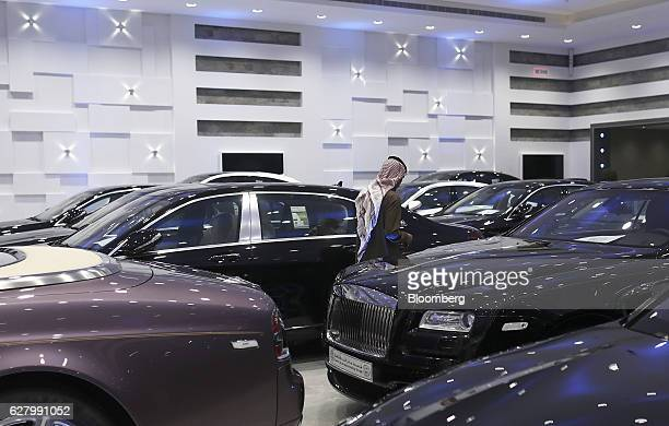 A customer browses a collection of luxury automobiles including a Rolls Royce Bentley and BMW whilst they stand on display at the Saden Al Araba...