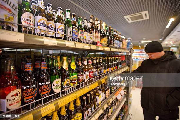 A customer browses a display of imported foreign beers and ciders for sale inside an Azbuka Vkusa OOO which translates as 'Elements of Taste'...