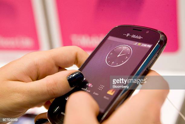 A customer browses a mobile phone at a TMobile store in London UK on Tuesday Nov 3 2009 Deutsche Telekom AG announce their 3Q earnings on Thursday...