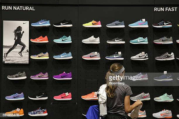 A customer browses a wall of Nike Inc sneakers on display for sale at Dick's Sporting Goods Inc store in Sterling Heights Michigan US on Thursday Aug...