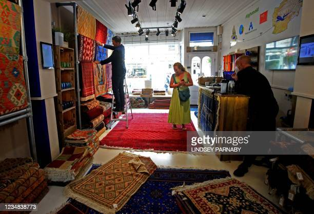 Customer browses at The Afghan Rug Shop in Hebden Bridge, northern England, on August 20, 2021. - Overseas businesses selling colourful handwoven...