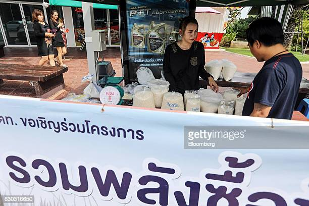 A customer browses bags of rice as farmer Suphatson Chanthamon center looks on at her stall in a PTT Pcl gas station in Ubon Ratchathani Thailand on...