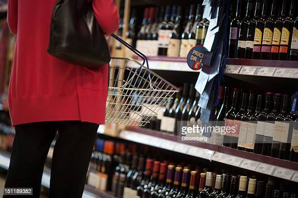 A customer browses bottles of red wine in the 'beers wines spirits' aisle of a supermarket in Slough UK on Monday Sept 3 2012 UK retail samestore...