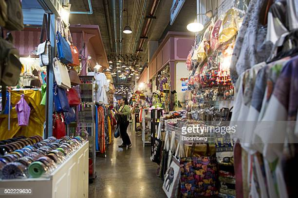 A customer browses clothing at a market stall at Asiatique The Riverfront openair mall in Bangkok Thailand on Friday Dec 18 2015 Thai economic...
