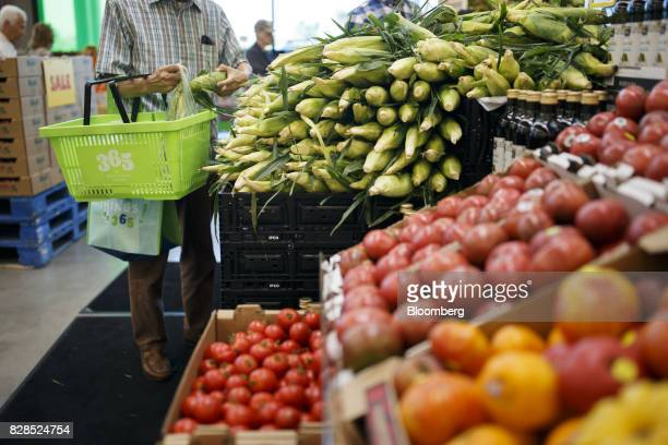 A customer browses fresh corn displayed for sale during the grand opening of a Whole Foods Market 365 location in Santa Monica California US on...