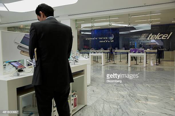 A customer browses mobile devices at an America Movil SAB Telcel service center in Mexico City Mexico on Tuesday July 21 2015 North America's...