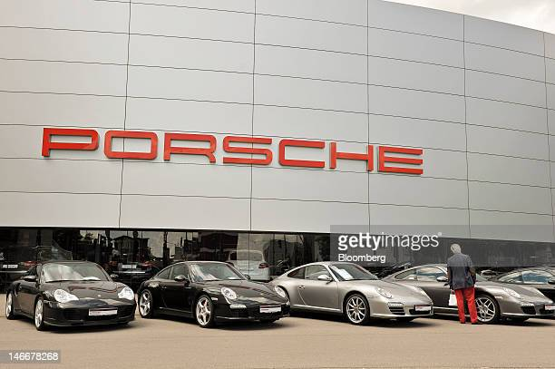 A customer browses Porsche 911 automobiles on display outside a dealership in Stuttgart Germany on Friday June 22 2012 Porsche AG which is jointly...
