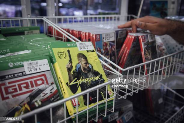 Customer browses products near a Cyberpunk 2077 computer game, produced by CD Projekt SA, for the Xbox games console in a video games store in Paris,...