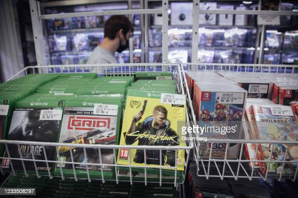Customer browses products near a Cyberpunk 2077 game, produced by CD Projekt SA, for the Xbox games console in a video games store in Paris, France,...