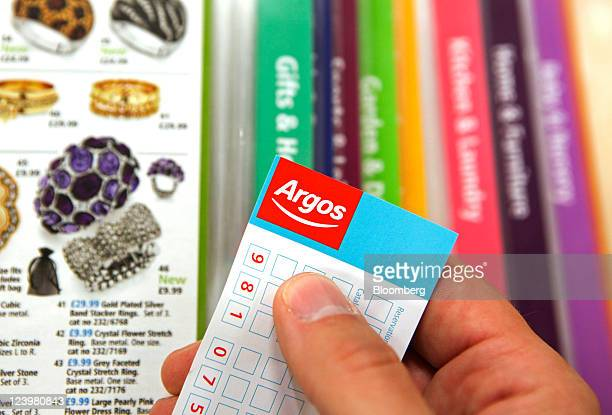 A customer browses the jewelry section of a catalogue at an Argos store operated by Home Retail Group Plc in Enfield UK on Wednesday Sept 7 2011 Home...