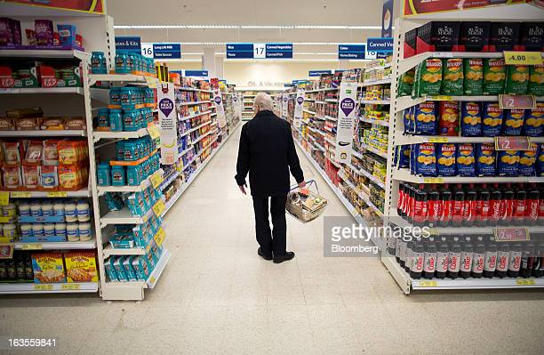 A customer browses tinned goods on display inside a Tesco Plc supermarket in the borough of Kensington in London UK on Tuesday March 12 2013 Tesco...