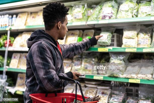 customer buying greens on supermarket - vegetarian food stock pictures, royalty-free photos & images