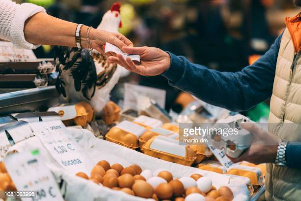 customer buying organic eggs at the farmer's market - agricultural fair stock pictures, royalty-free photos & images