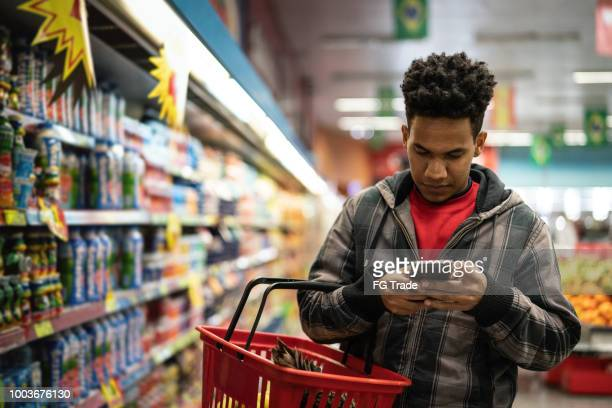 customer buying with mobile app on supermarket - brazilian men stock photos and pictures